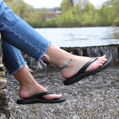 Women's Sol Bounce Ara Flip Flop in Black on figure, model sitting on a rocky ledge over a small river waterfall, feet dangling off the side over the water