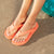 Closeup on the Ara Flip Flop in Coraline on figure in the sand. Female model sitting on a pool float