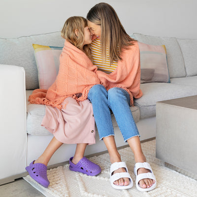 Female model with her daughter snuggling on the couch, bot wearing their Sol Bounce Sandals