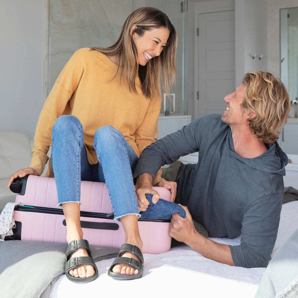 Female model sitting on a suitcase and laughing while wearing her Molded Buckle Sol Bounce. Male model is trying to pull a pair of jeans out of the suitcase and laughing