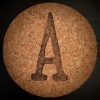 a round cork lid on black background with capital letter A stamped in black
