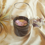 matte black candle jar with purple succulents and glass bell cover with fabric backdrop airplant and amethyst crystal