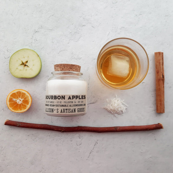 flatlay on white plaster: glass candle with wick lid surrounded by apple and orange, applewood stick, shredded coconut, rocks glass of bourbon, and cinnamon stick