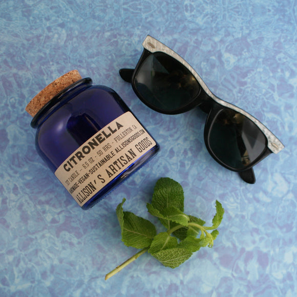 close up of standard candle recycled glass cork lid apothecary inspired kraft label on pool water background with mint and sunglasses