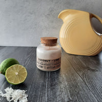 signature glass candle jar with cork on aged wood counter, fresh sliced lime and shaved coconut in foreground, bright yellow pitcher in background