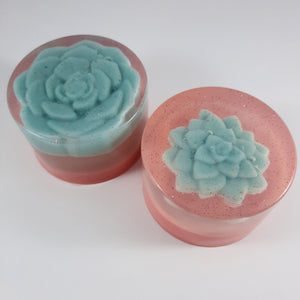 cylinder of clear soap with bioglitter and embedded succulent on peachy background