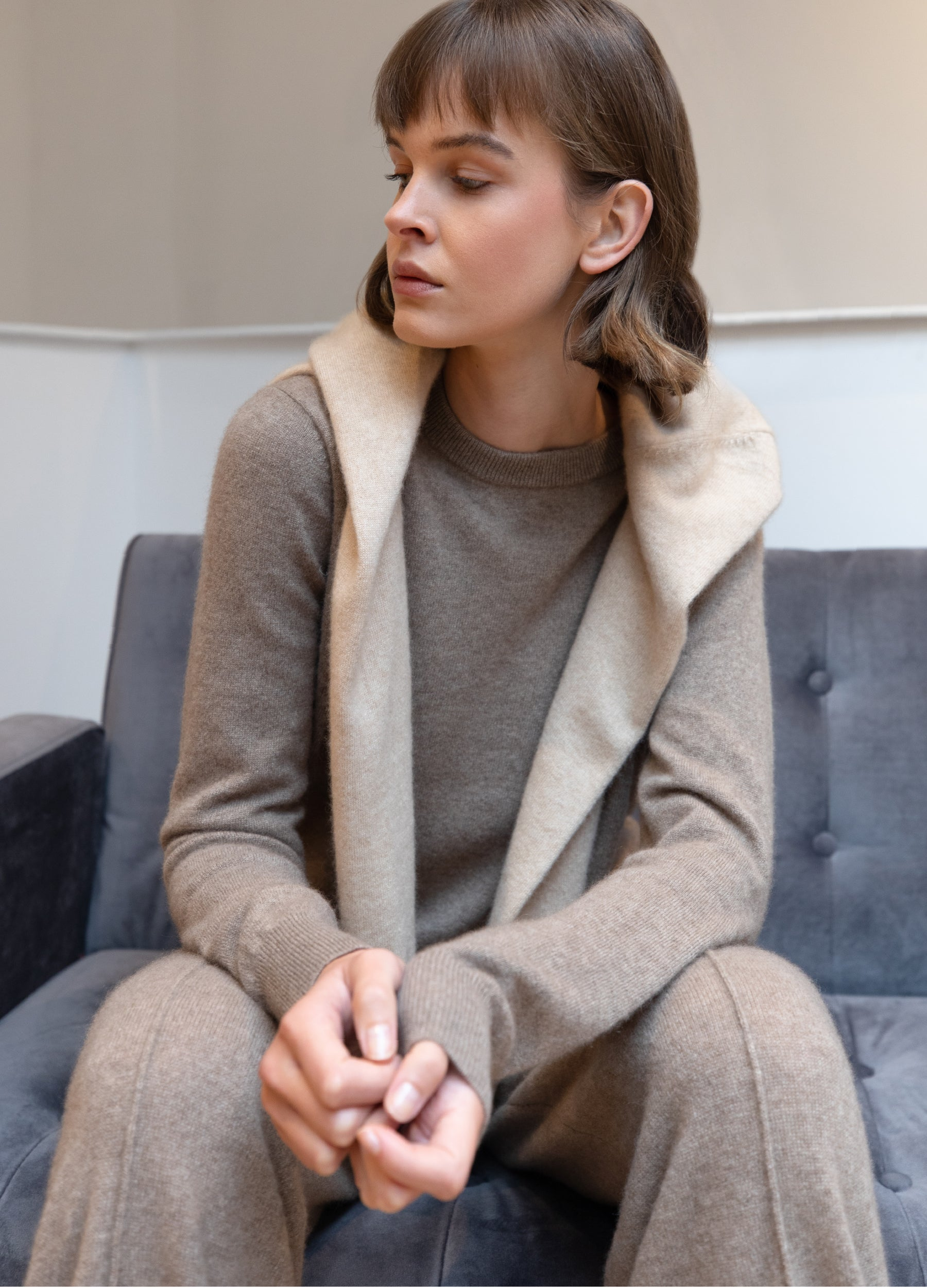 Brunette model wearing Les Cent Ciels undyed cashmere jumper and trousers while sitting on a sofa