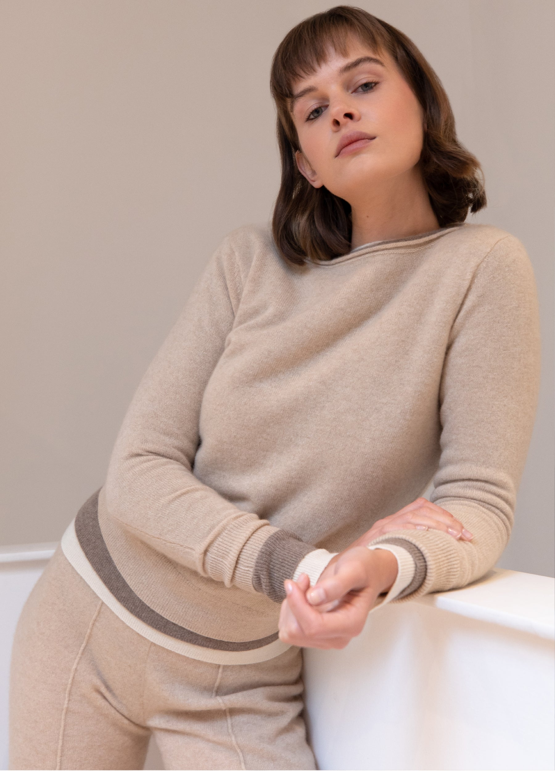 Brunette model wearing Les Cent Ciels undyed cashmere jumpers and trousers and leaning over a half wall