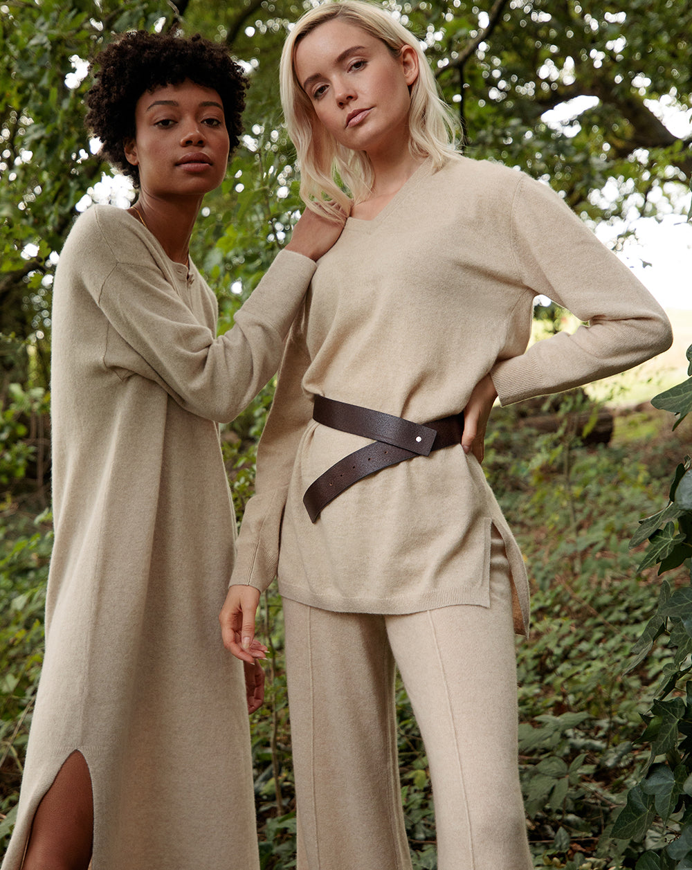 Black model wearing Les Cent Ciels tunic cashmere dress alongside blonde model wearing cashmere tunic top and trousers, both in undyed beige cashmere