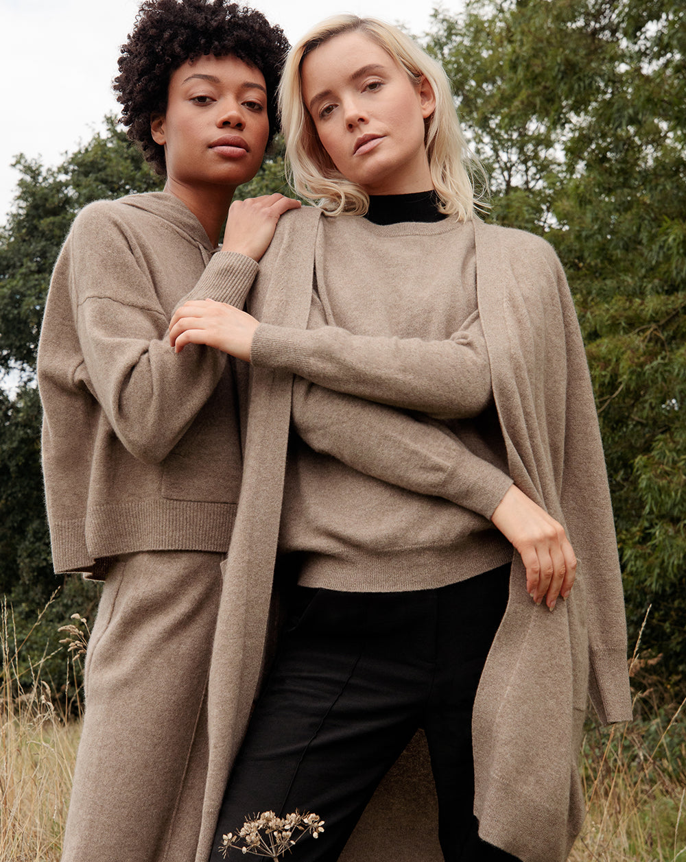 Black model wearing Les Cent Ciels dark brown cashmere hoodie and trousers alongside blonde model wearing a dark brown crew neck jumper and cardigan over it with black trousers,