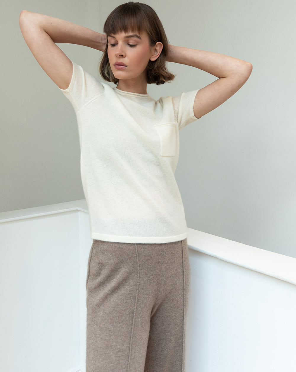 Brunette model wearing an ecru Les Cent Ciels cashmere tee and cashmere brown trousers