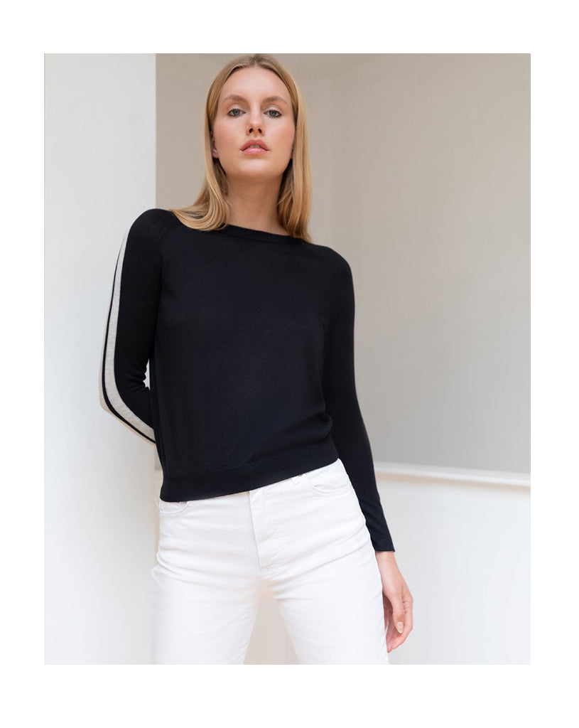 Blonde model wearing Les Cent Ciels knitted black jumper with stripe detail on the sleeves