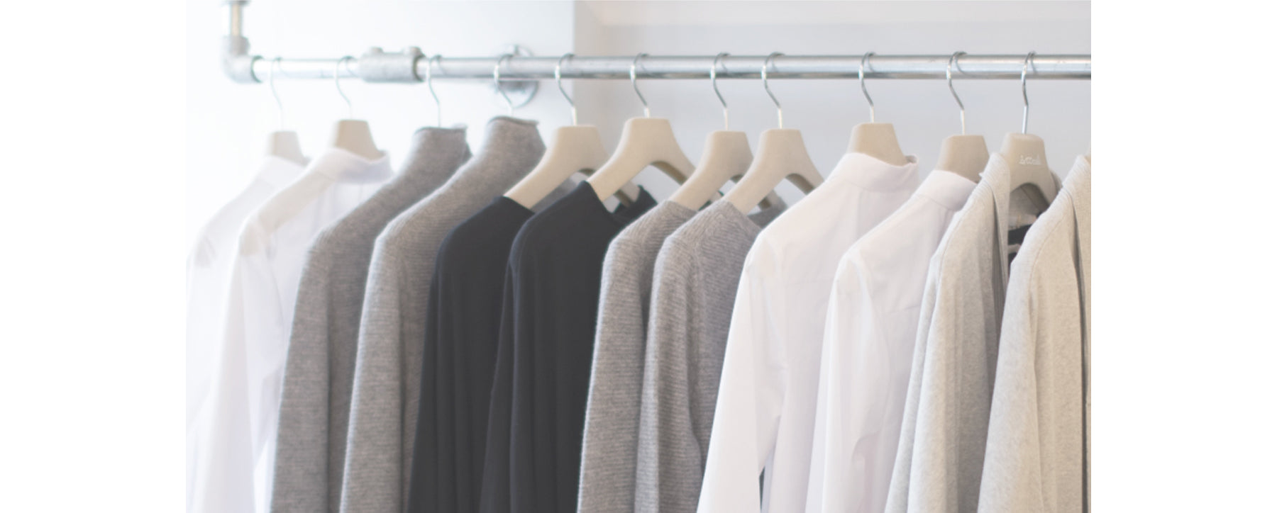 Les Cent Ciels essential garments on a silver rail over a white neutral background