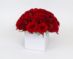 Flower arrangement - Amor. Red roses & red spray roses in a white vase. Side view.