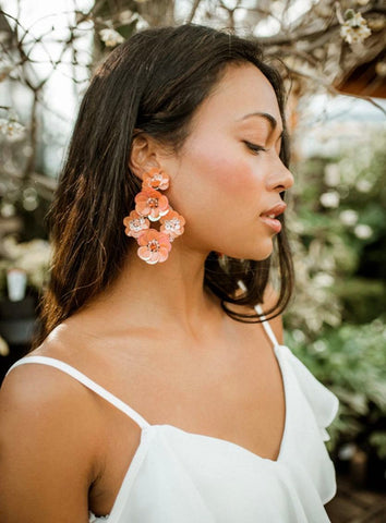 woman wearing coral sequin floral earrings