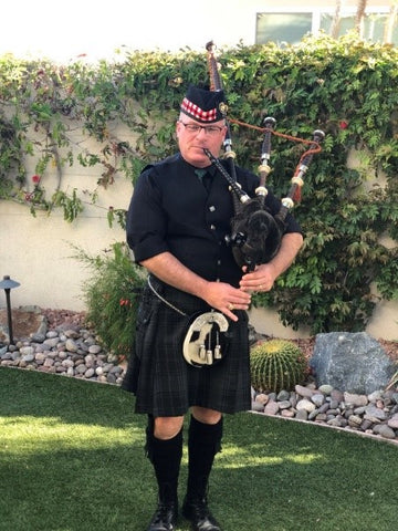 man playing bagpipes in a backyard