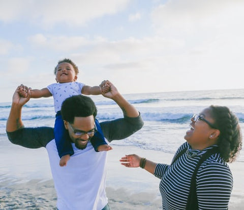 two adults and a toddler laughing on the beach for mothers day