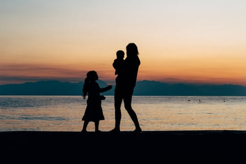 mom and two children photoshoot at sunset on beach for mothers day