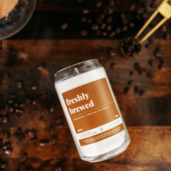 a coffee fragranced freshy brewed candle atop a wooden butcher block countertop