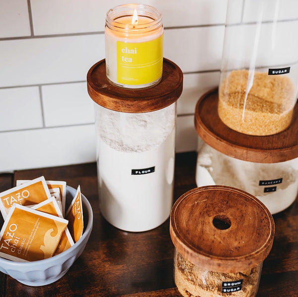 an herbal chai tea candle sits brightly lit upon kitchen canisters with subway tile back splash