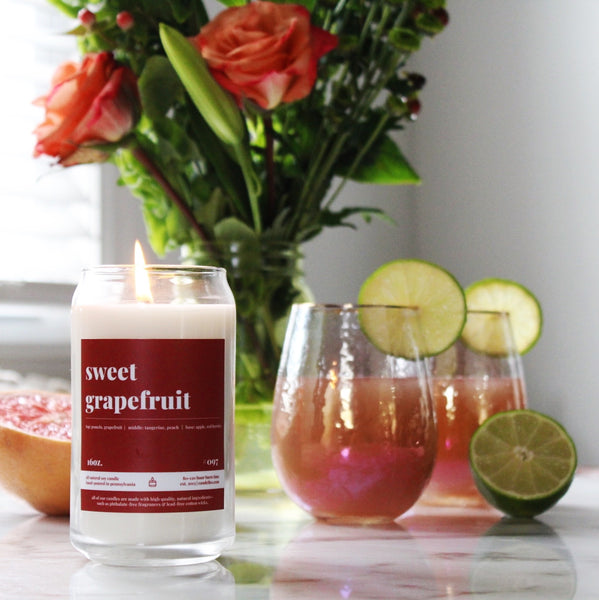 a sweet grapefruit fragranced candle burns brightly sitting atop a table new two custom crafted grapefruit cocktails