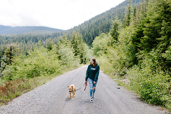 Nyah Gray of Gray and Hound walks neighbor dog Sputze along a beautiful serene trail in the Pacific North West