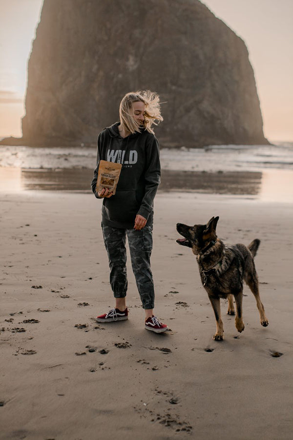 Nyah Gray of Gray and Hound with a dog on a beautiful beach in the Pacific North West