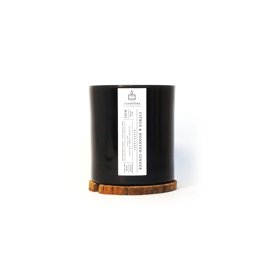 Soy Candle in Citrus & Honeyed Ginger scent in a sleek black tumbler featuring a minimalist white label and displayed on a wooden coaster