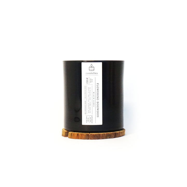 Soy Candle in Flowering Dogwood scent in a sleek black tumbler featuring a minimalist white label and displayed on a wooden coaster