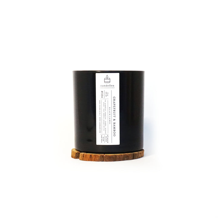Soy Candle in Grapefruit & Bamboo scent in a sleek black tumbler featuring a minimalist white label and displayed on a wooden coaster
