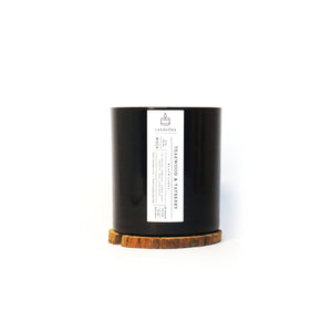 Soy Candle in Teakwood & Tayberry scent in a sleek black tumbler featuring a minimalist white label and displayed on a wooden coaster
