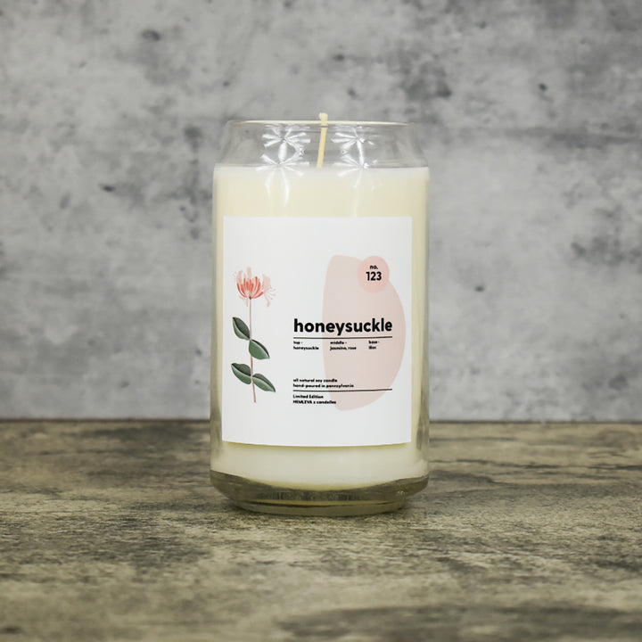 Honeysuckle scent soy wax candle in can shaped glass vessel with tapered top and beautifully minimal label with pastel shapes and a floral drawing from our Hemleva Collaboration
