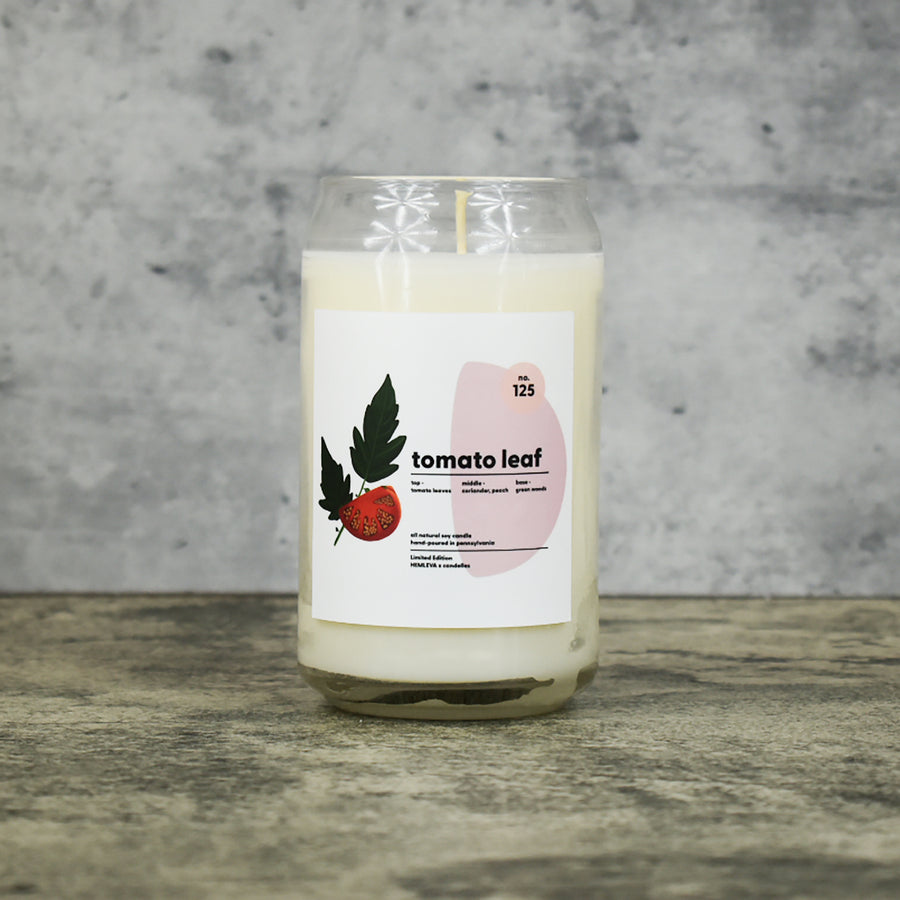 Tomato Leaf scent soy wax candle in can shaped glass vessel with tapered top and beautifully minimal label with pastel shapes and a mint leaf drawing from our Hemleva Collaboration