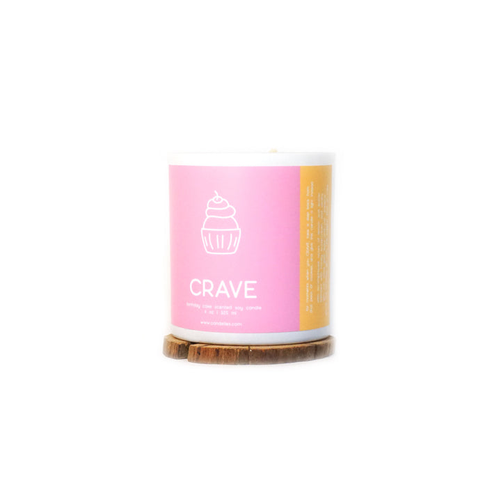 Soy Candle in the Crave scent in a sleek white tumbler featuring a vibrant pink and orange label with graphic imagery showing a cupcake, this candle is displayed on a wooden coaster