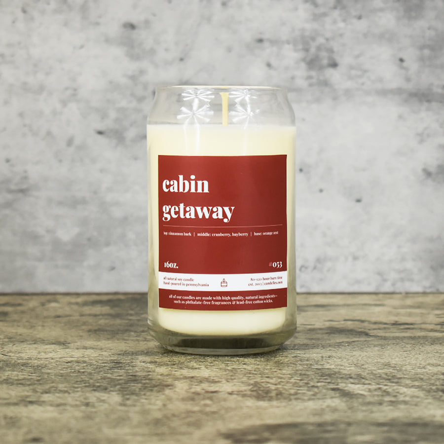 Cabin Getaway scent soy wax candle in can shaped glass vessel with tapered top and rich reddish brown label