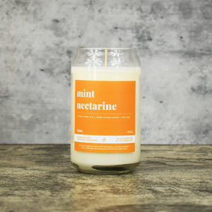 Mint Nectarine scent soy wax candle in can shaped glass vessel with tapered top and bright orange label