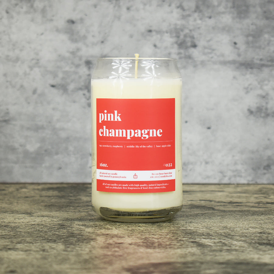 Pink Champagnescent soy wax candle in can shaped glass vessel with tapered top and bright pink label