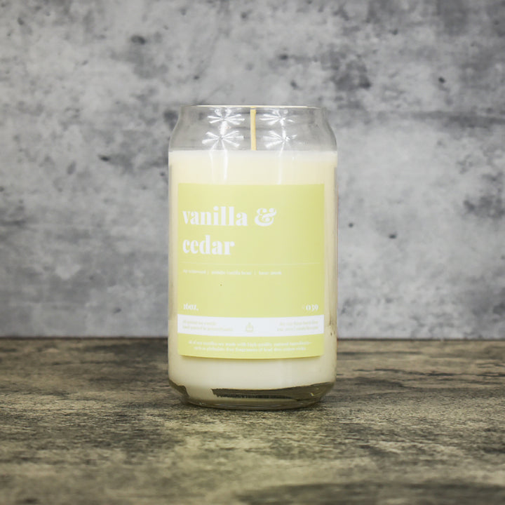 Vanilla and Cedar scent soy wax candle in can shaped glass vessel with tapered top and pale yellow-green label