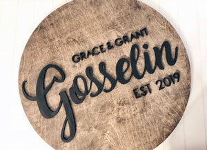 Round wood guestbook sign with custom 3d name and details, perfect for rustic weddings.