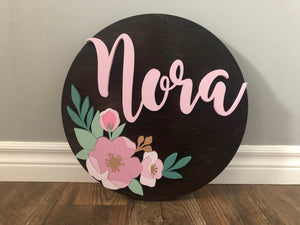 Round nursery name sign with floral accents