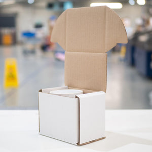 Photo of a recyclable cardboard box with the lid open showing a mug nestling safely inside