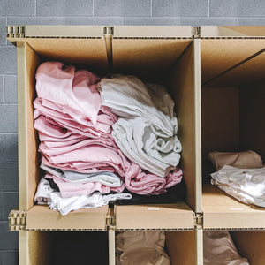 Photo of a cardboard storage rack in a warehouse with pigeon holes storing t-shirts ready to be printed onto