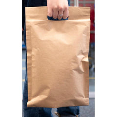 Photo of someone carrying a recyclable paper mailing bag with the hand through the paper handle at one end of the bag
