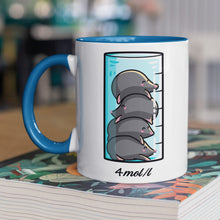Load image into Gallery viewer, A chemistry beaker filled with 4 cute moles design on a two toned blue and white ceramic mug, shown on top of a magazine
