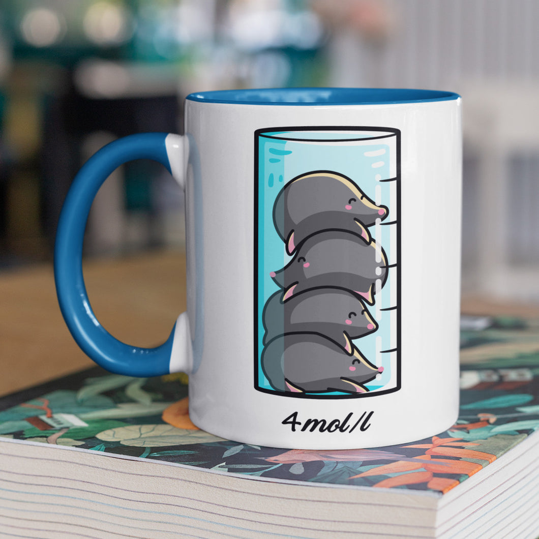 A chemistry beaker filled with 4 cute moles design on a two toned blue and white ceramic mug, shown on top of a magazine