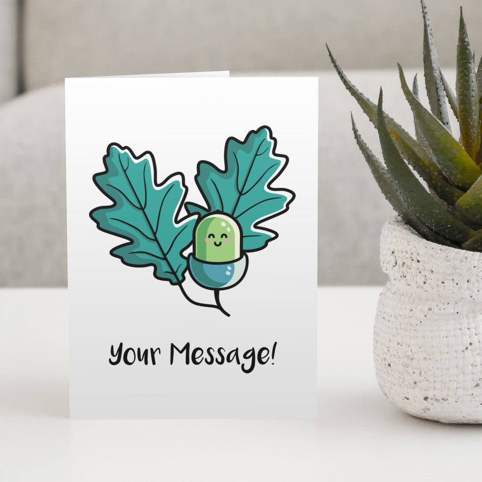 A white greeting card standing on a white table with a design of a kawaii cute green acorn with two oak leaves behind on either side and the words your message written beneath