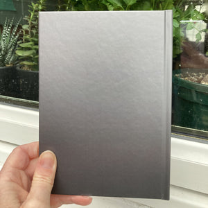 Hardback journal held in a hand showing the dark grey back