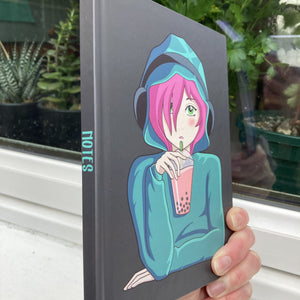 Dark grey hardback journal held in a hand side on showing the word notes written on the spine and an anime girl with pink hair on the front