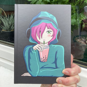 Grey hardback journal held in a hand showing the front with a picture of an anime girl with pink hair and green eyes wearing a green hoodie and headphones drinking boba