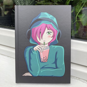 Grey hardback journal standing front facing with a picture of an anime girl with pink hair and green eyes wearing a green hoodie and headphones drinking boba
